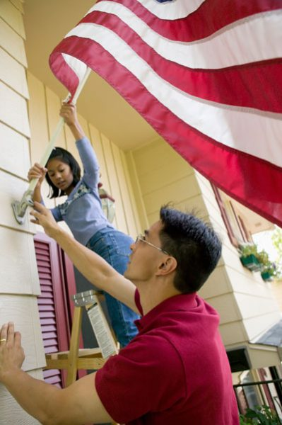 Immigrant Family hangs an American flag.