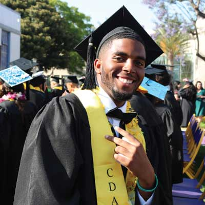 Smiling young African American male college graduate