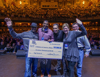 Sebastian Maniscalco presents a $17,000 check to the Volunteers of America of Illinois to benefit local veterans.